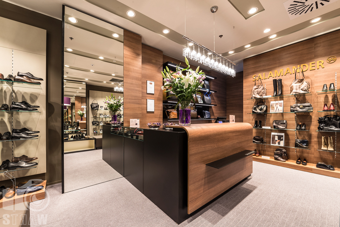 Fotografia wnętrz komercyjnych, zdjęcia salonu sprzedaży Salamender, lustro i kwiaty na ladzie.
