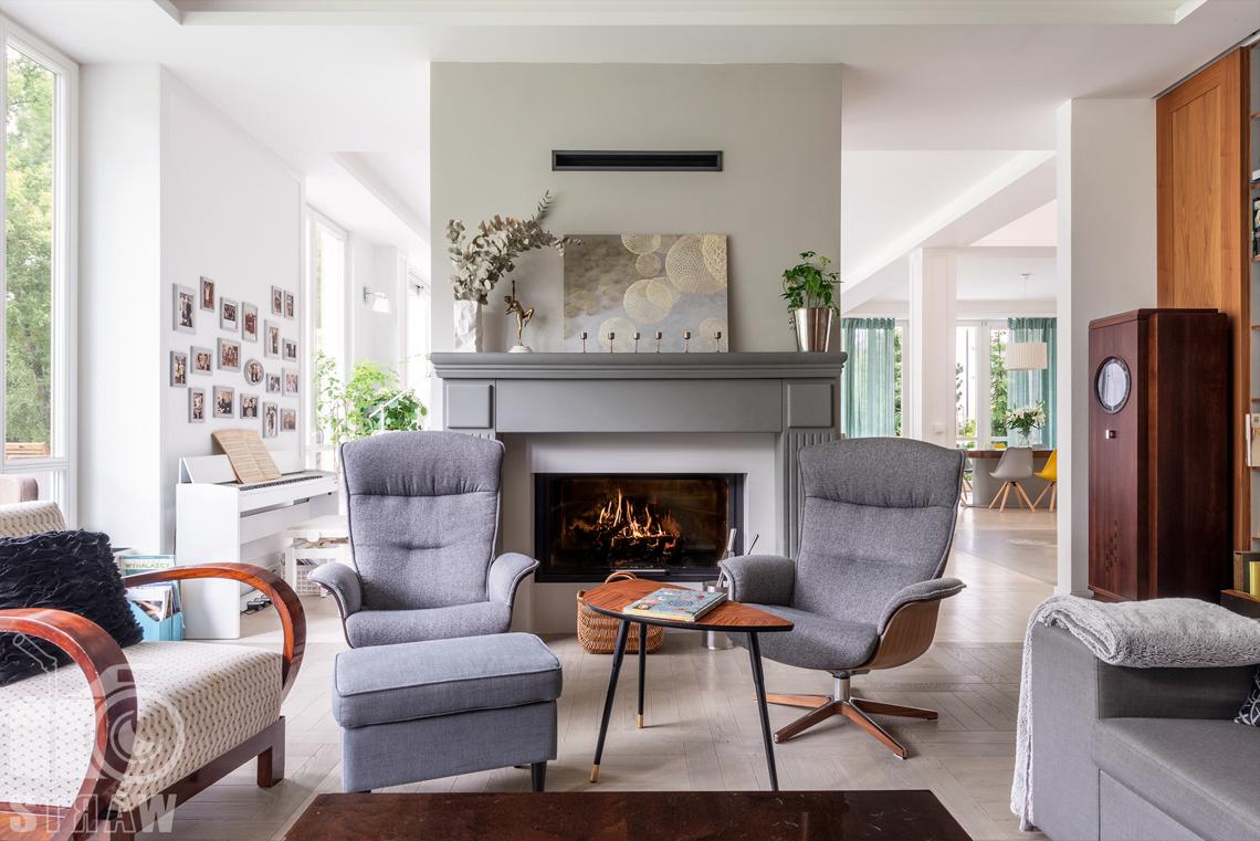 Zdjęcia nieruchomości na wynajem, fotografie domu i posesji, kominek, fotele w strefie wypoczynkowej.