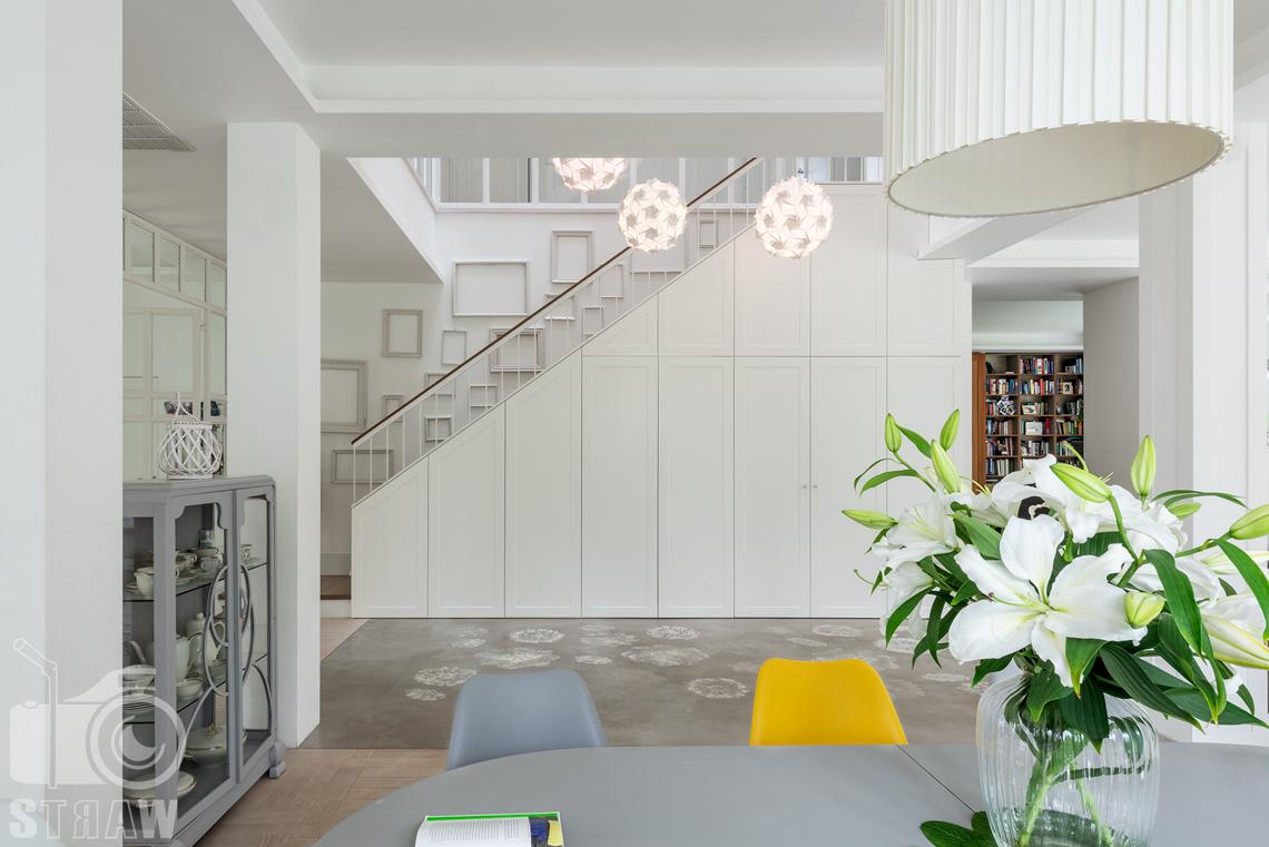 Fotografia nieruchomości na wynajem, zdjęcia domu z posesją zlokalizowanego w warszawskim Wilanowie, tutaj stół jadalni i widok na hol i schody.