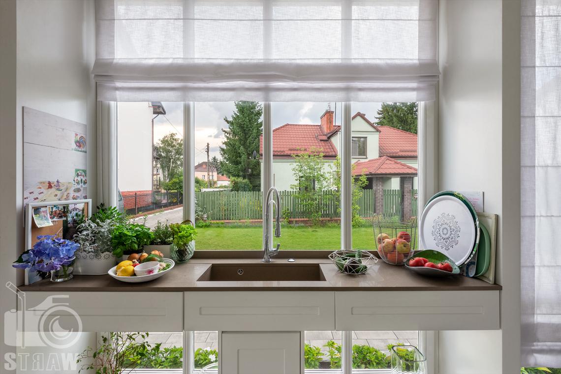 Zdjęcia wnętrz domu, tutaj okno w kuchni i zlew.