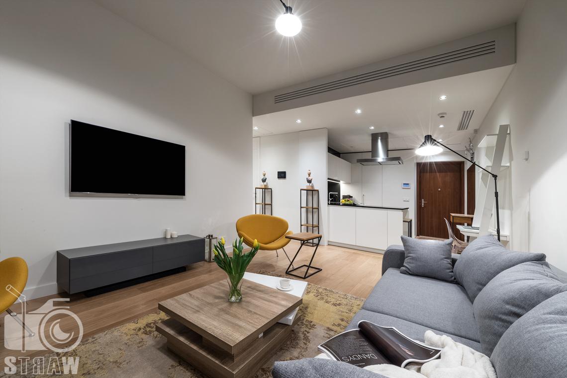 Sesja fotograficzna wnętrz apartamentu dla Mzuri, zdjęcia w apartamentowcu Złota 44, tutaj salon i kuchnia.