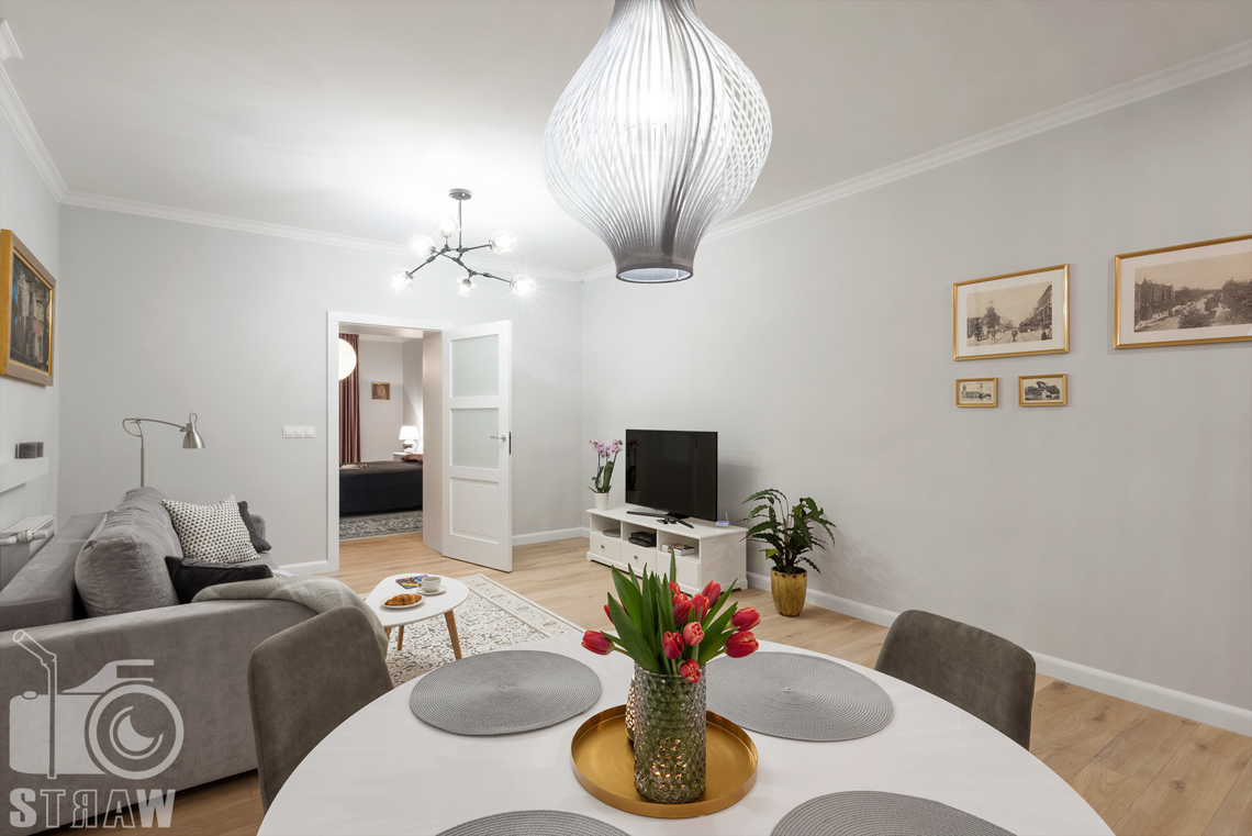 Fotograf apartamentu na wynajem krótkoterminowy booking com i airbnb zdjęcia wnętrz, stół w salonie i sypialnia.