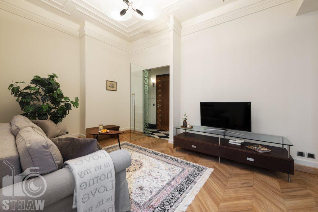 Fotograf apartamentów na wynajem krótkoterminowy airbnb i booking, apartament przy ulicy Hożej w Warszawie. salon z sofą i stolikiem pod telewizor.
