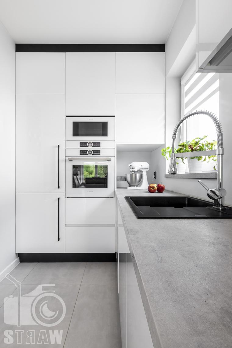 Fotografia wnętrz, zdjęcia zabudowy kuchennej dla producenta mebli, zabudowa biało czarna, blat szary.