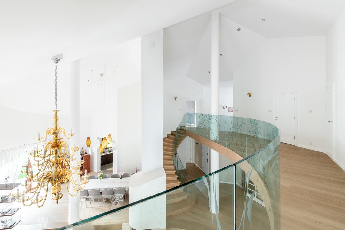Fotografia wnętrza domu zaprojektowanego przez biuro projektowe, antresola widoczne duże żyrandole w salonie i jadalni.