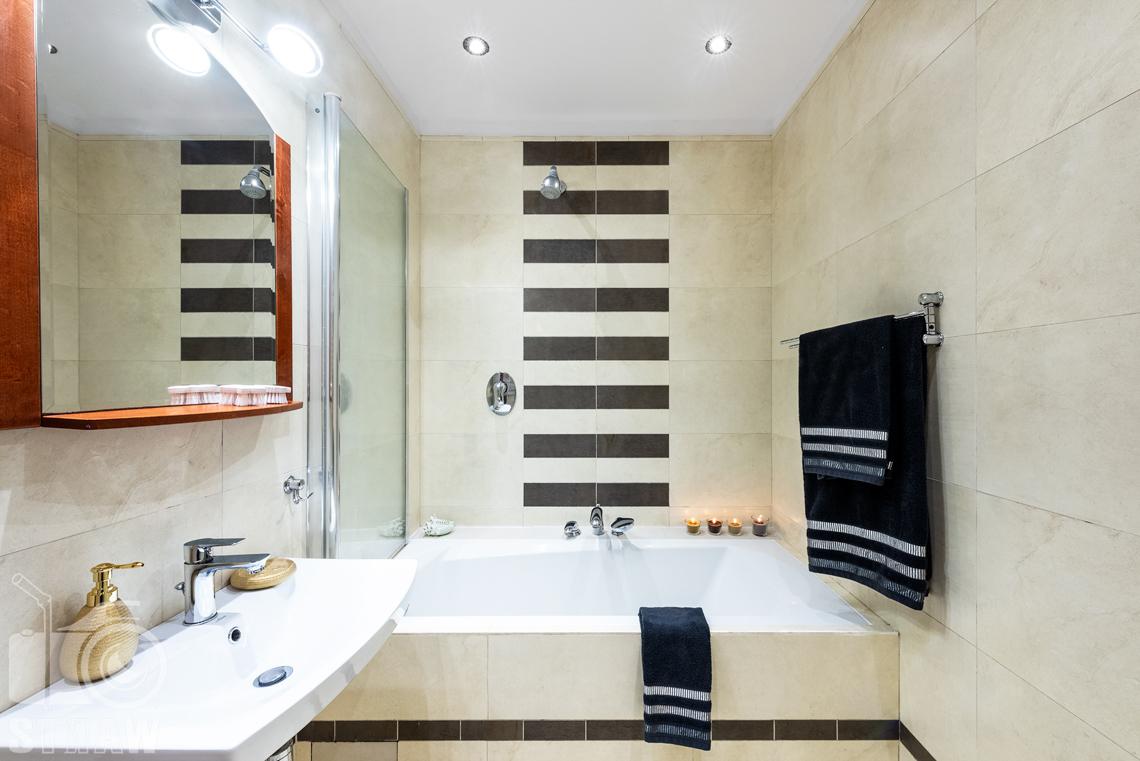 Sesja fotograficzna mieszkania na sprzedaż, łazienka z wanną w ciepłej tonacji żółtej.