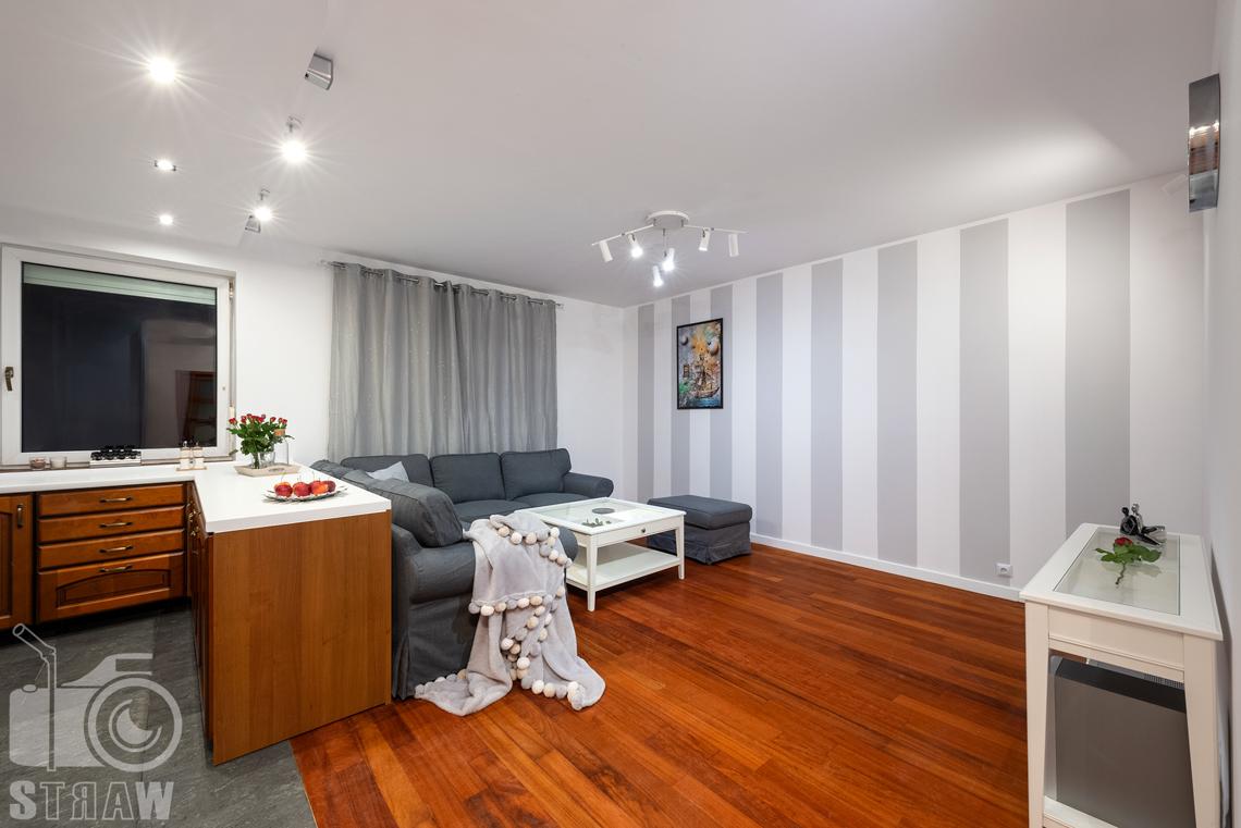 Sesja fotograficzna mieszkania na sprzedaż kuchnia i salon z tapeta w pasy pionowe.