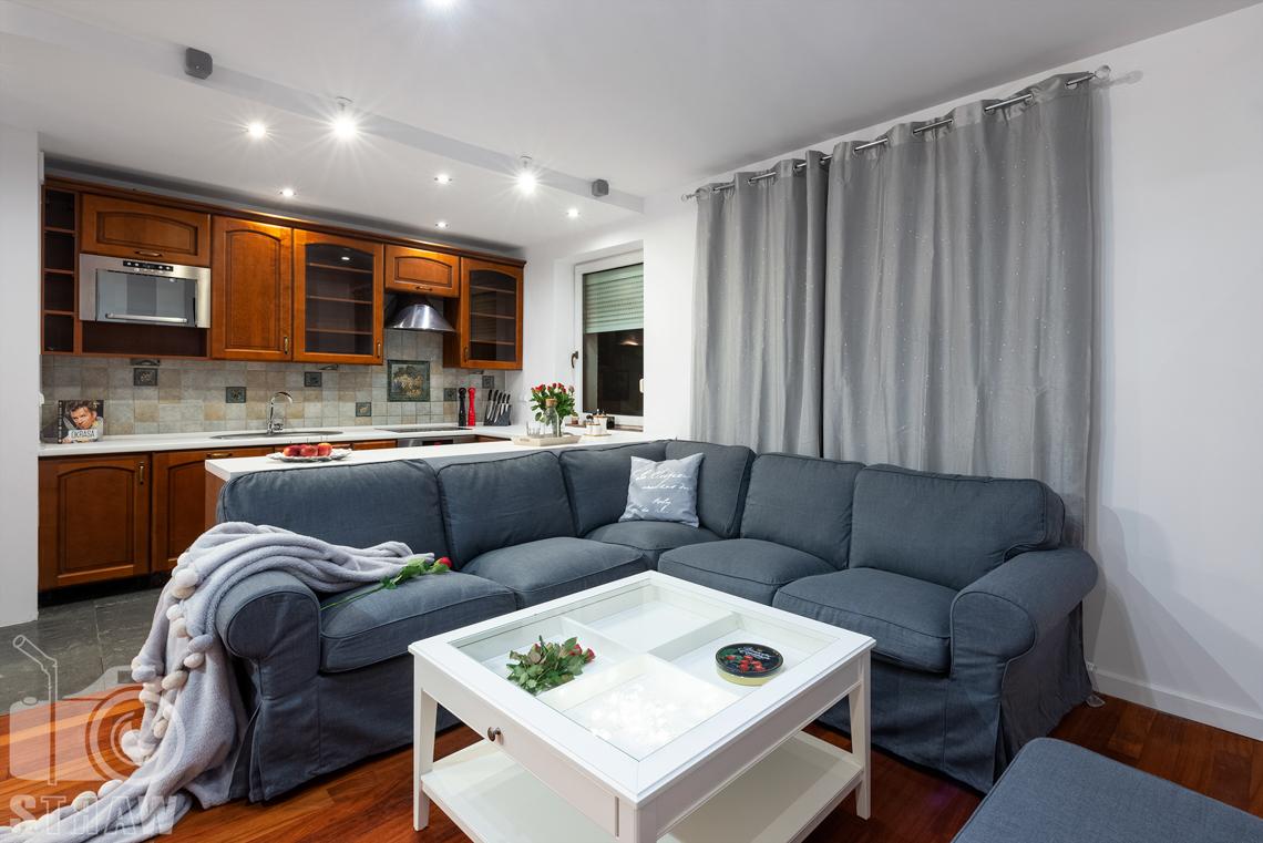 Sesja fotograficzna mieszkania na sprzedaż tutaj narożnik w salonie oraz otwarty aneks kuchenny.