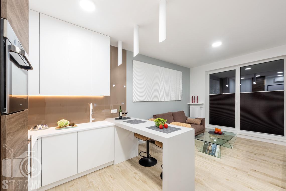 Fotografia nieruchomości na wynajem krótkoterminowy, kuchnia, stolik bufetowy i salon.