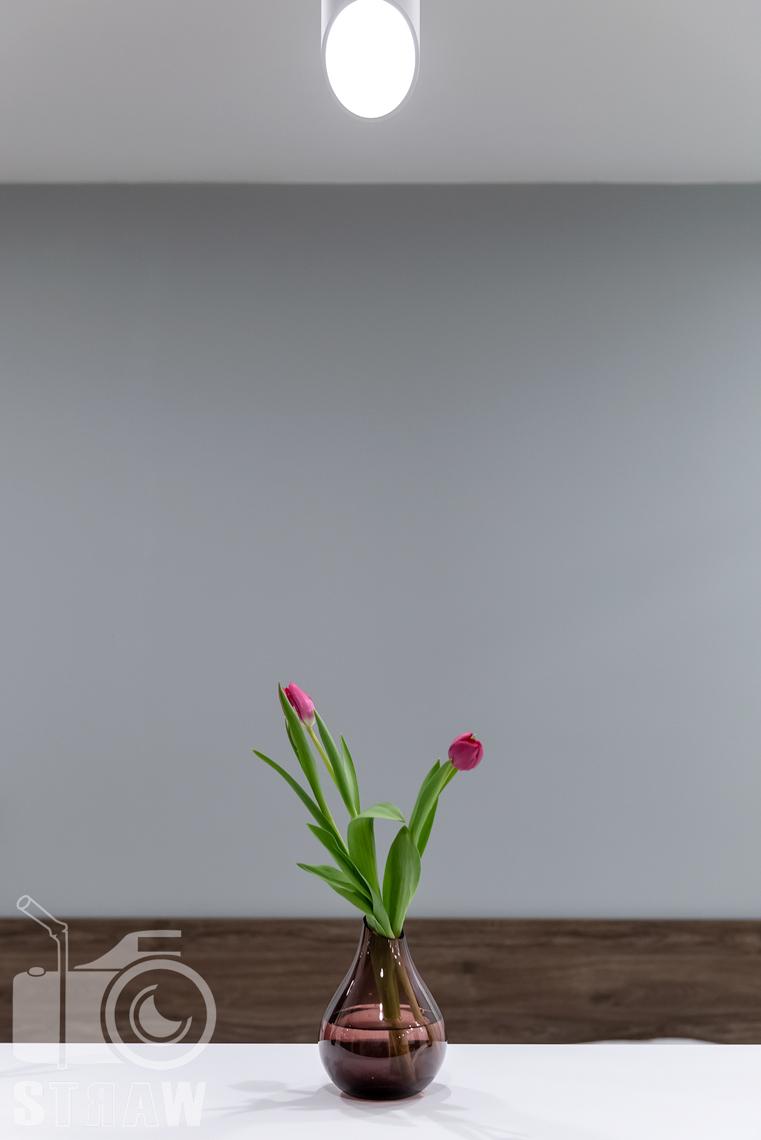 Fotografia nieruchomości na wynajem krótkoterminowy, tulipany stanowiące przybranie ścianki działowej pomiędzy salonem i sypialnią.