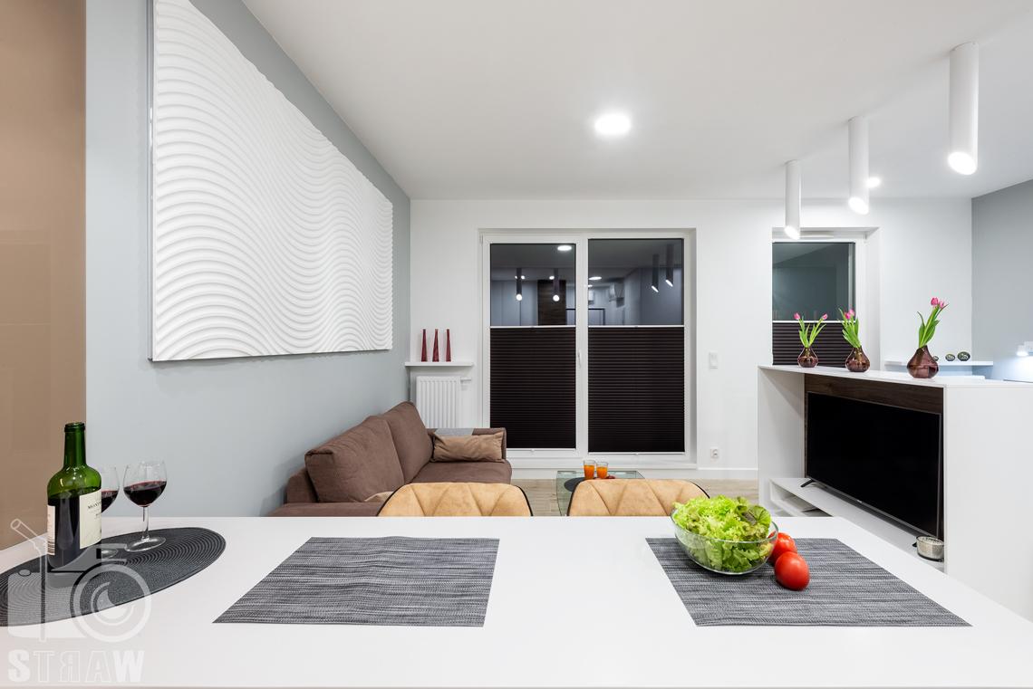 Fotografia nieruchomości na wynajem krótkoterminowy na zdjęciu widok na salon od strony kuchni i stołu bufetowego.
