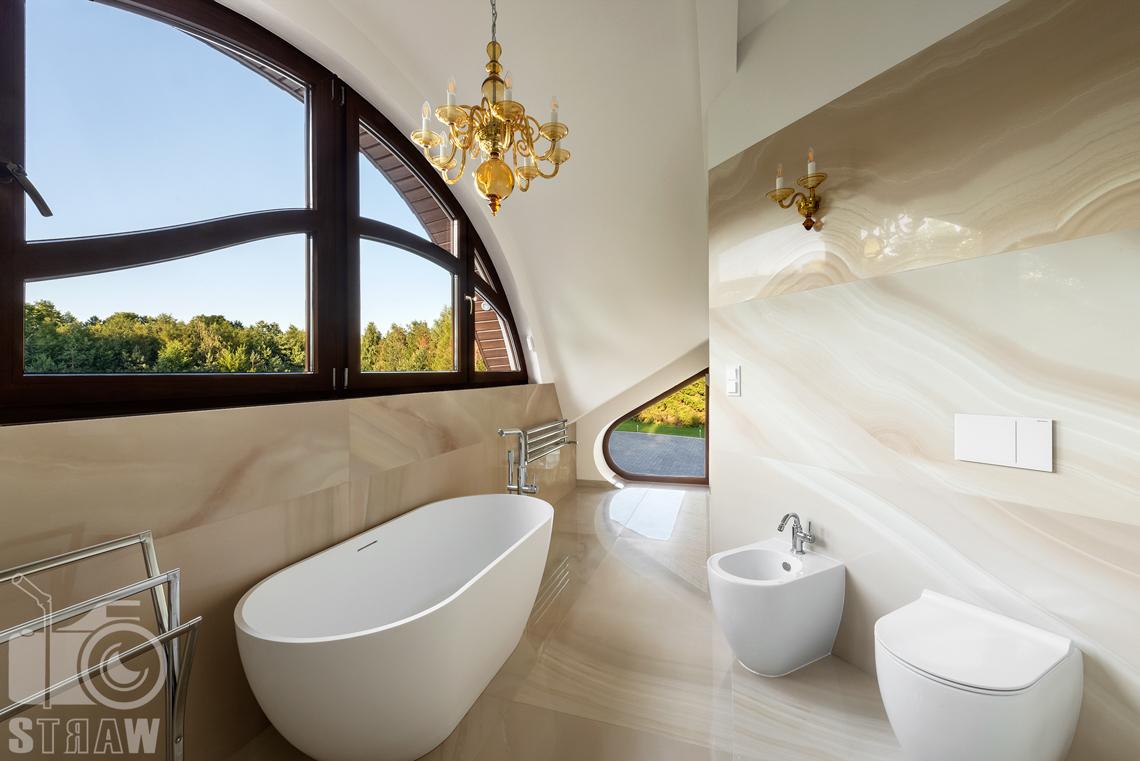 Fotografia wnętrz domu zaprojektowanego przez biuro projektowe, główna łazienka z wanną i oknami.