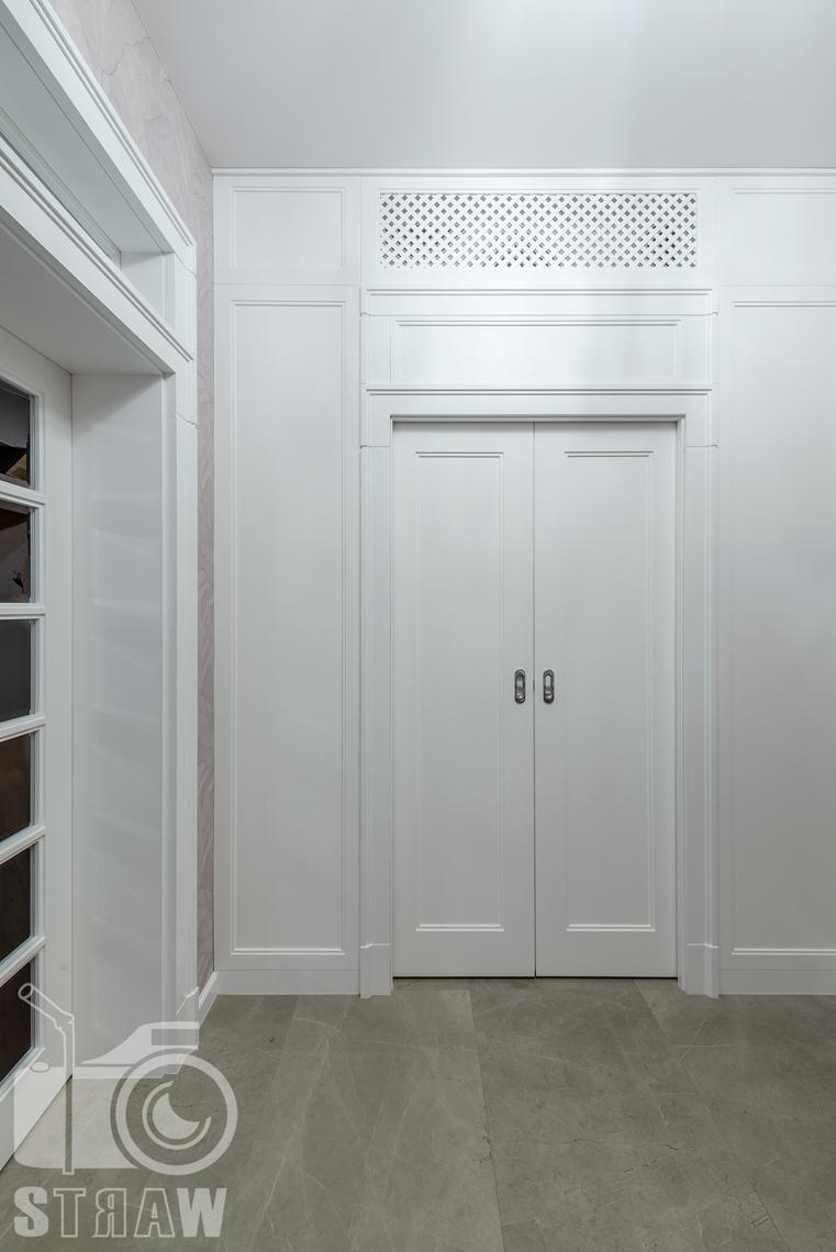 Fotografia wnętrz domu zaprojektowanego przez biuro projektowe, przedpokój, drzwi do garderoby.