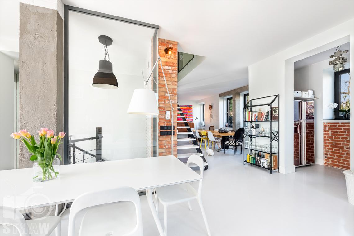 Fotografia nieruchomości na sprzedaż, zdjęcia wnętrza domu w miejscowości Konstancin Jeziorna, tutaj jadalnia w kuchni i duży stół w salonie.