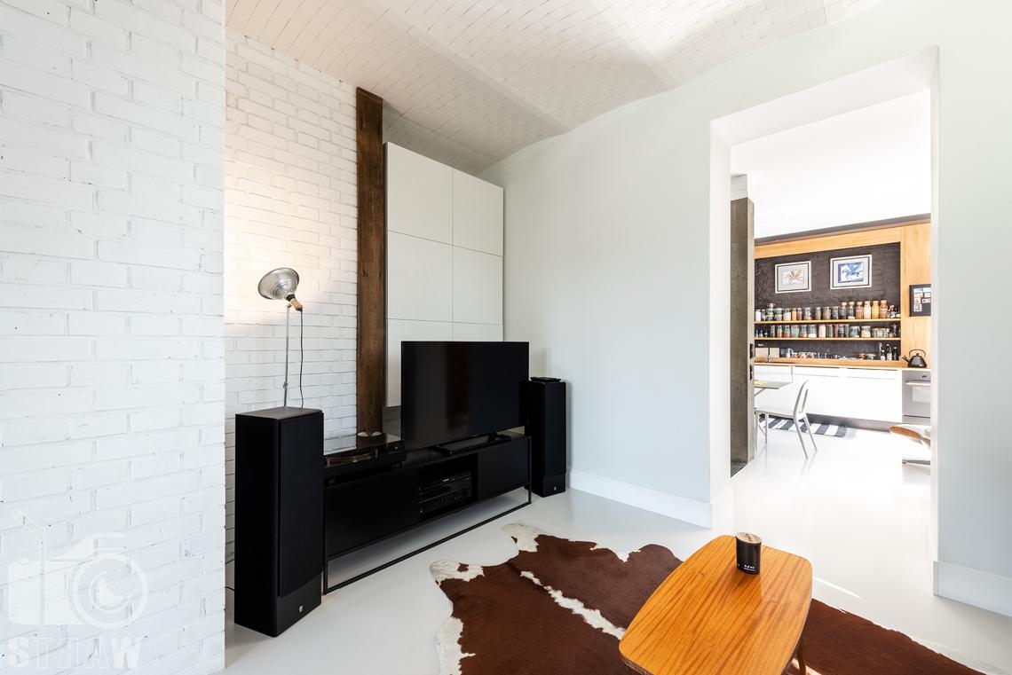 Fotografia nieruchomości na sprzedaż, zdjęcia wnętrza, na zdjęiu kącik telewizyjny w miejscu odrestaurowanej mykwy.