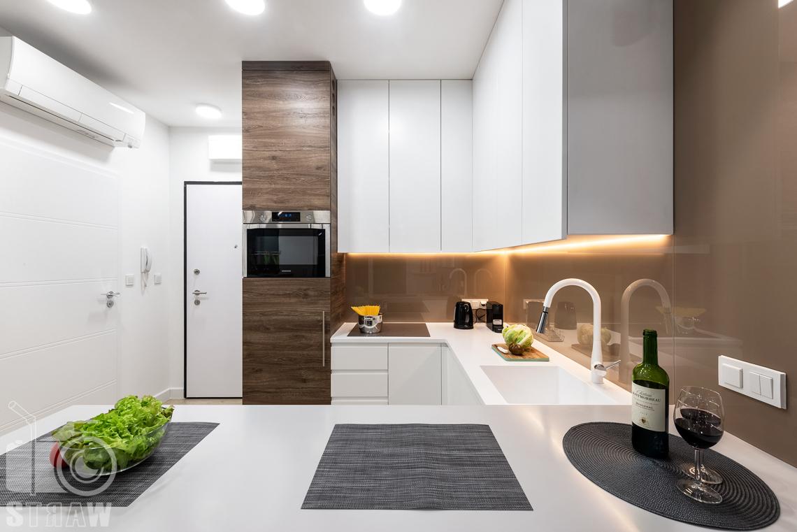 Fotografia nieruchomości na wynajem krótkoterminowy, widok na otwartą kuchnię od strony pokoju.