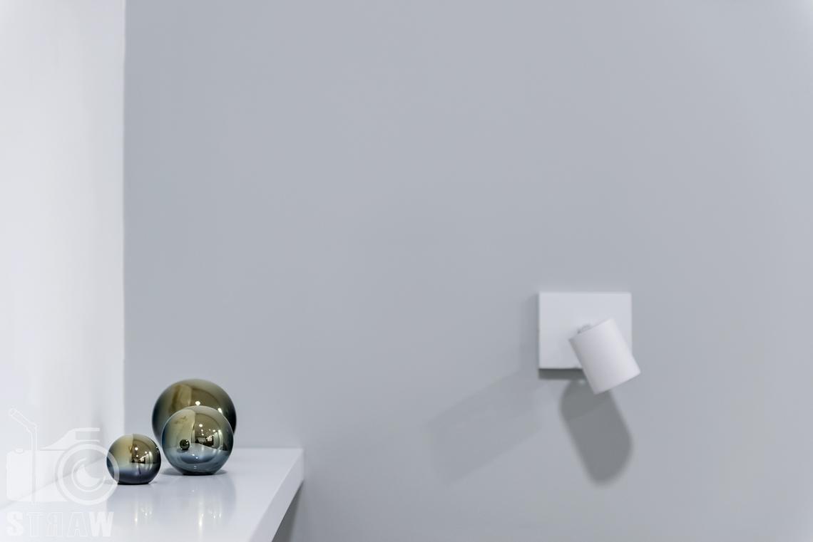 Fotografia nieruchomości na wynajem krótkoterminowy detale w sypialnie, lampka i ozdoby na szafce nocnej.