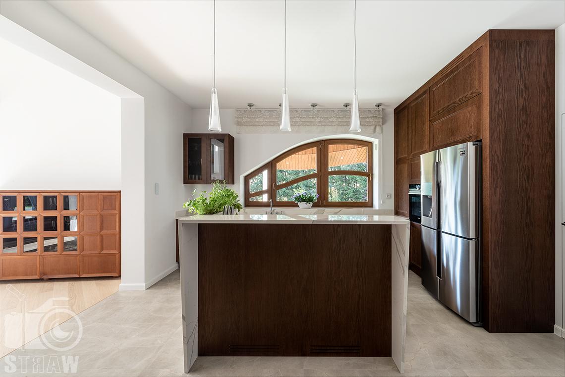 Fotografia wnętrz domu zaprojektowanego przez biuro projektowe, kuchnia, wyspa kuchenna i wiszące lampy.