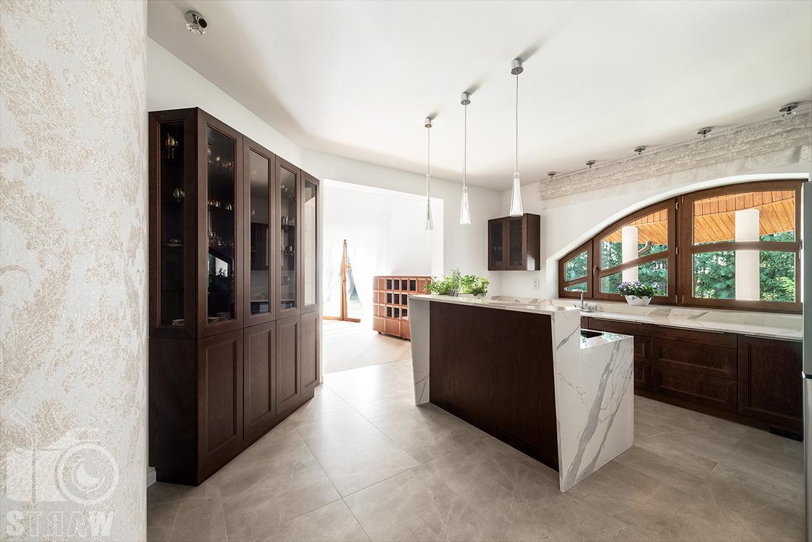 Fotografia wnętrz domu zaprojektowanego przez biuro projektowe, kuchnia, regał przeszklony, wyspa i przejście do jadalni.