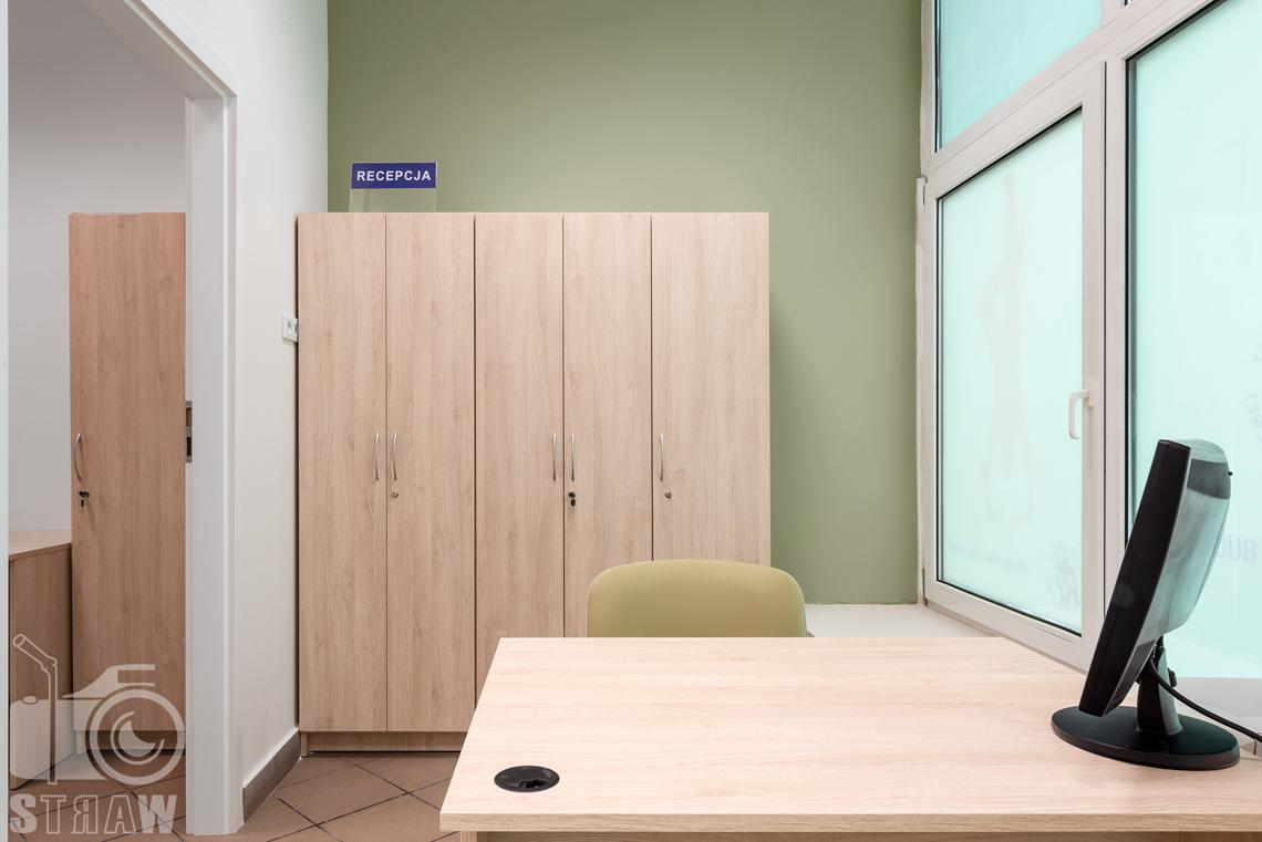 Fotografia wnętrz komercyjnych, zdjęcia domu opieki medycznej recepcja z biurkiem, szafą i monitorem.