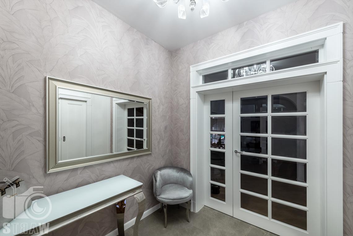 Fotografia wnętrz domu zaprojektowanego przez biuro projektowe, przedpokój widok w stronę salonu, przeszklone drzwi.