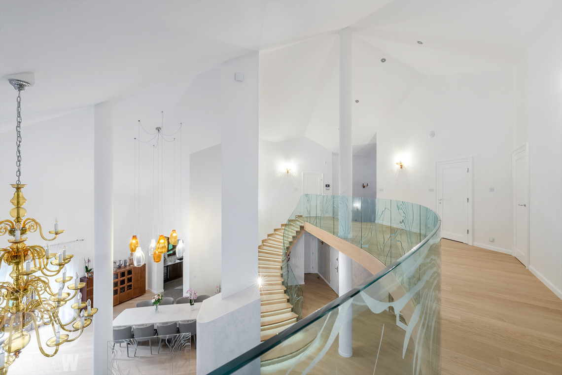 Fotografia wnętrz domu zaprojektowanego przez biuro projektowe, antresola, widok na salon i jadalnię.