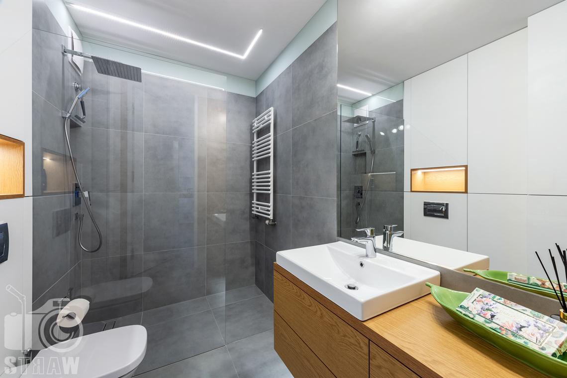 Fotografia wnętrz, zdjęcia apartamentu na wynajem, łazienka w tonacji szarej, białej i drewnianej.