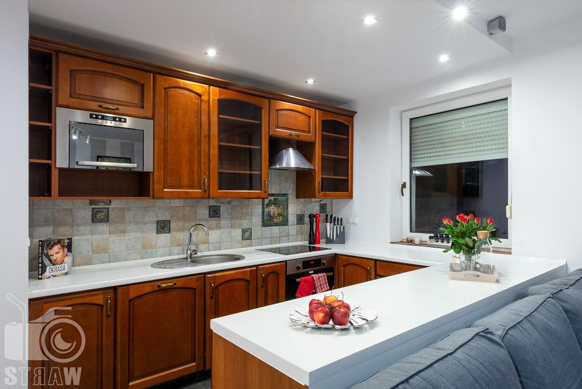 Sesja fotograficzna mieszkania na sprzedaż blat kuchenny z dekoracją i otwarta kuchnia.