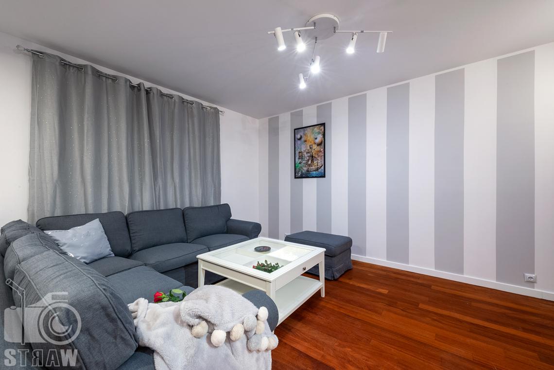 Sesja fotograficzna mieszkania na sprzedaż, salon duży narożnik i tapeta w pasy.
