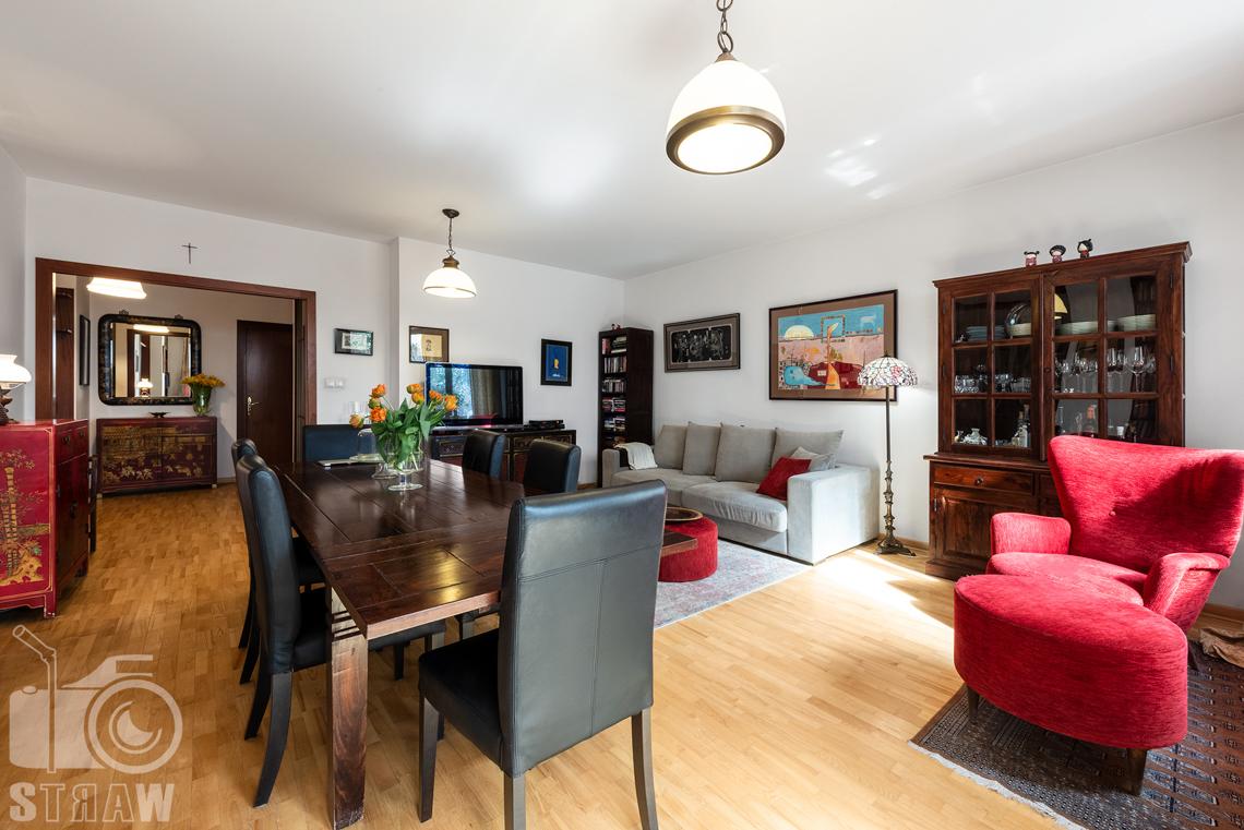Zdjęcia nieruchomości na sprzedaż tutaj salon duży stół i szara sofa.