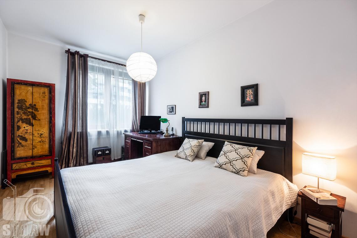 Zdjęcia nieruchomości na sprzedaż sypialnia z dużym łóżkiem i biurkiem.