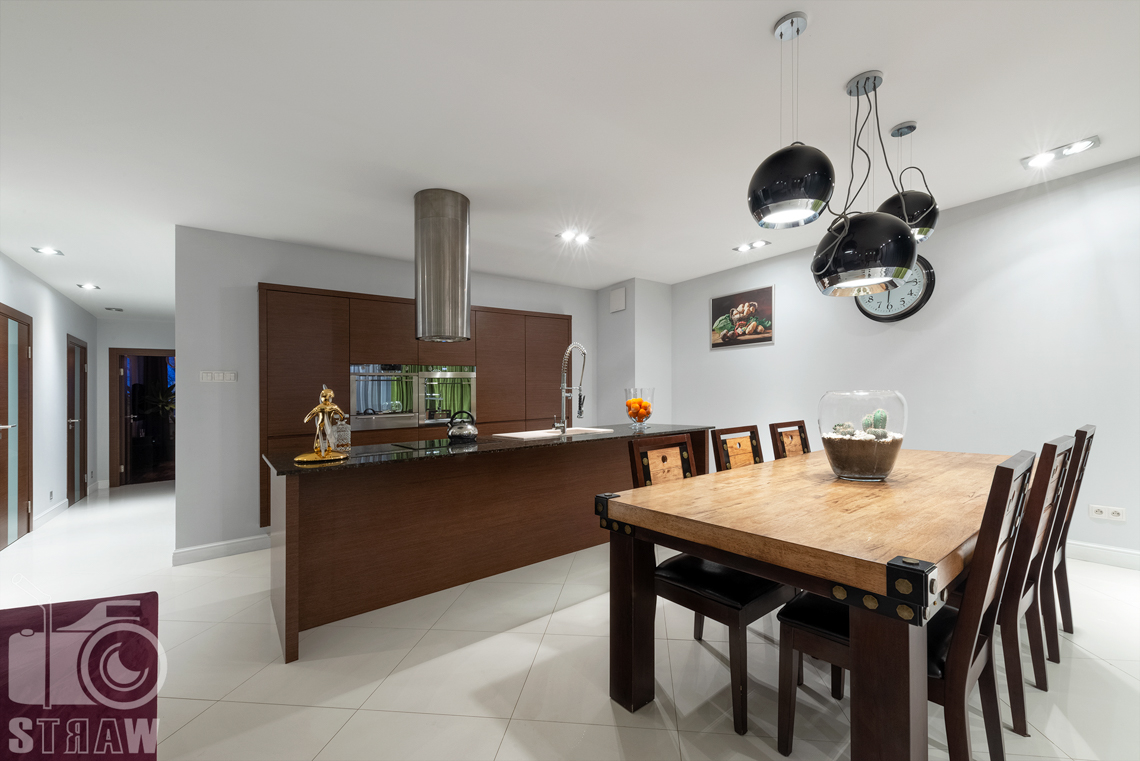 Zdjęcia mieszkania na sprzedaż w Warszawie na Bielanach, tutaj jadalnia z drewnianym stołem i otwarta kuchnia.