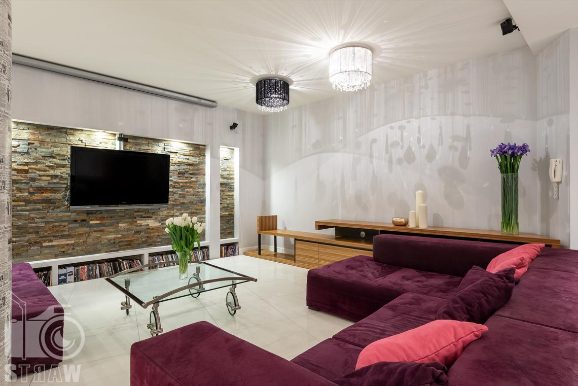 Zdjęcia mieszkania na sprzedaż na warszawskich Bielanach, salon, bordowa sofa i stolik kawowy.
