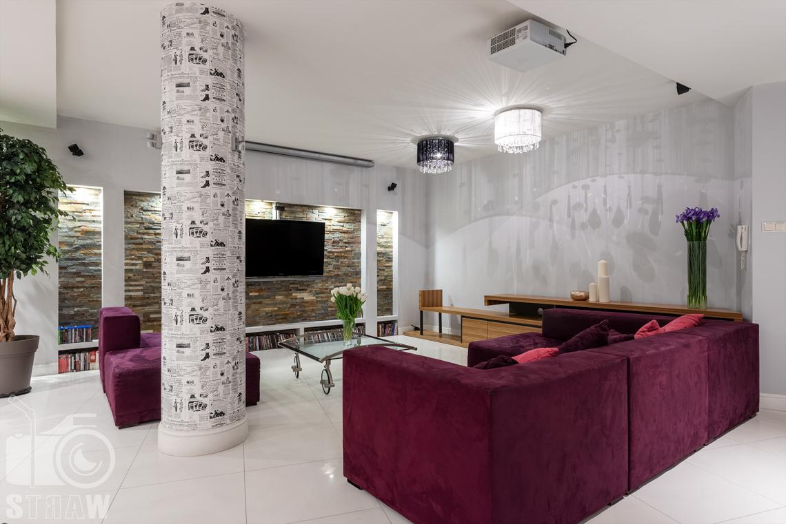 Zdjęcia mieszkania na sprzedaż w Warszawie, sofa i wytapetowana kolumna.