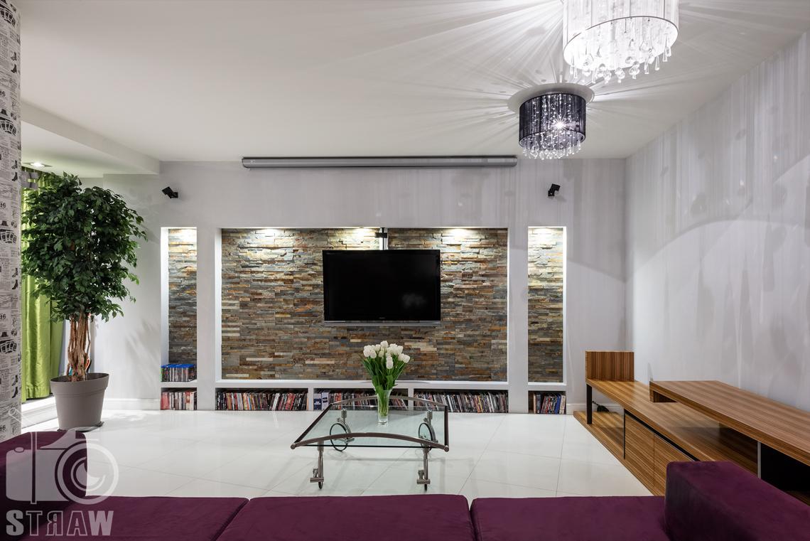 Zdjęcia mieszkania na sprzedaż, stolik kawowy i ściana w telewizorem.