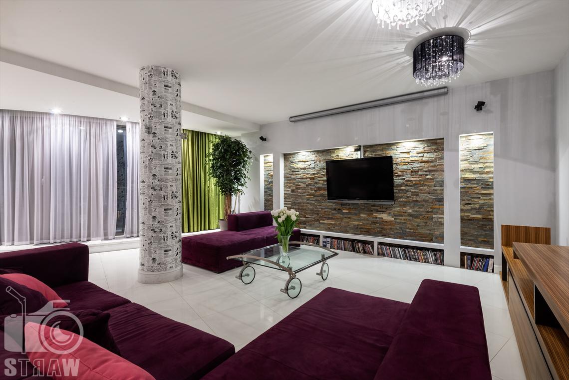 Zdjęcia mieszkania na sprzedaż na Bielanach w Warszawie, salon z dużą sofą podzielopną na dwie części oraz stolik kawowy na kółkach.
