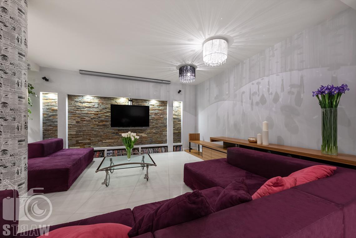 Zdjęcia mieszkania na sprzedaż w Warszawie, na zdjęciu wnętrza salon z dwoma żyrandolami, czarnym i białym.