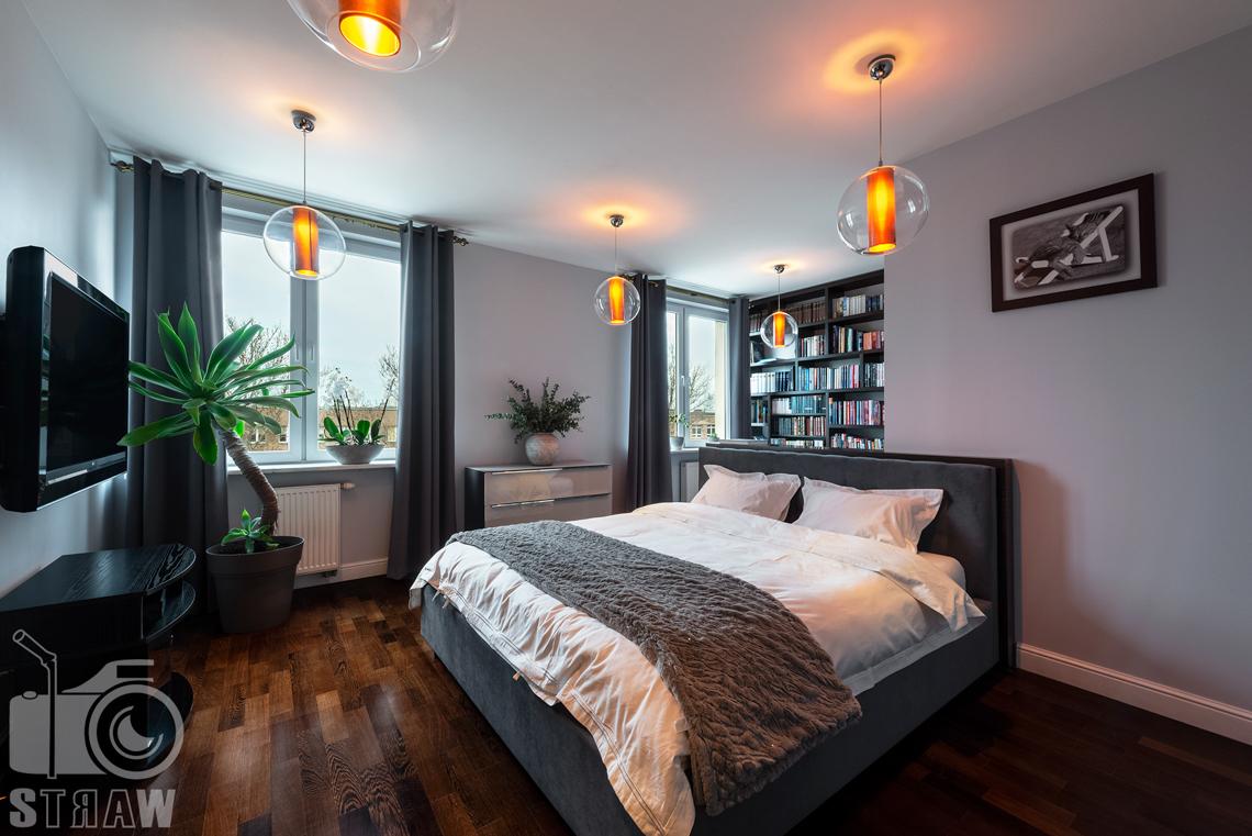 Zdjęcia mieszkania na sprzedaż w Warszawie, sypialnia z klimatycznymi pomarańczowymi lampami.