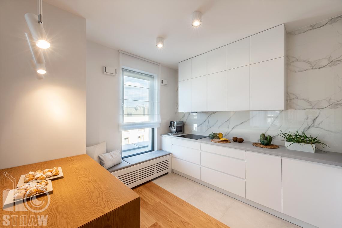Fotografia wnętrz dla projektantów, zdjęcia mieszkania wykończonego według projektu biura projektowego 4ma Projekt, kuchnia, siedzisko pod oknem i zabudowa kuchenna.