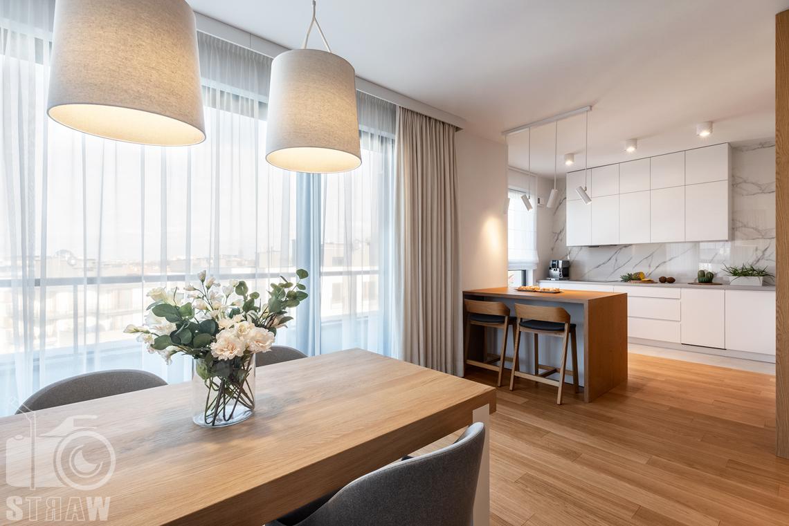 Fotografia wnętrz dla projektantów, zdjęcia mieszkania wykończonego według projektu biura projektowego 4ma Projekt, przy stole w salonie, z widokiem na kuchnię.