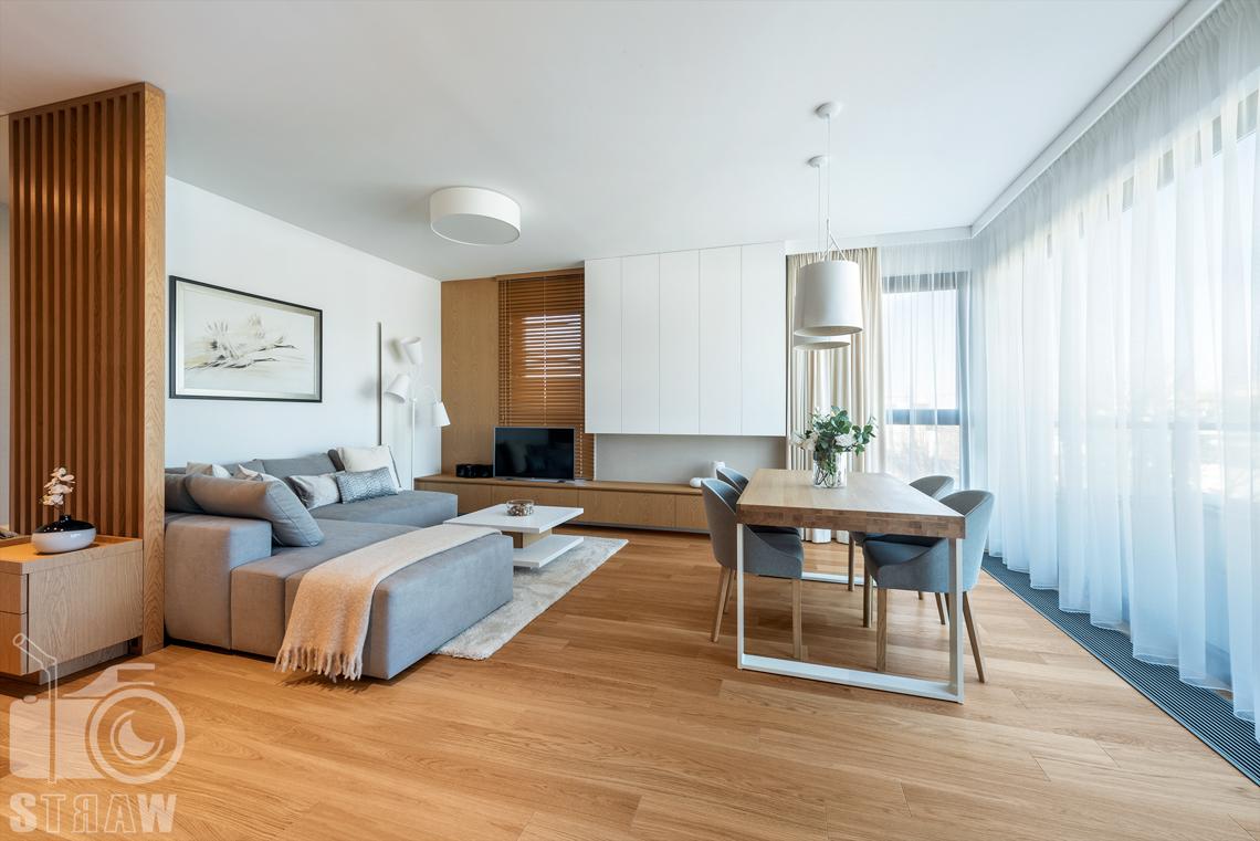 Fotografia wnętrz dla projektantów, zdjęcia mieszkania wykończonego według projektu biura projektowego 4ma Projekt, salon z dużym stołem i sofą.