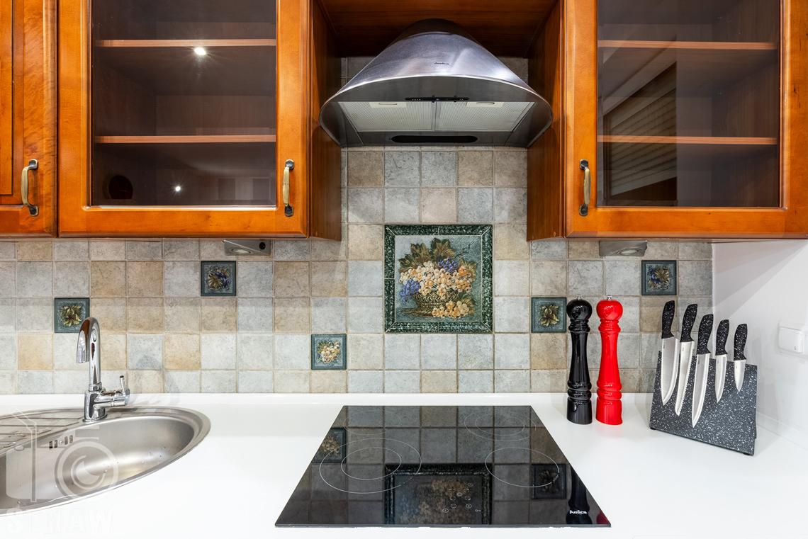 Sesja fotograficzna mieszkania na sprzedaż, kuchnia z blatem kuchennym i płytą grzewczą.