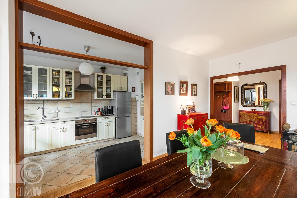 Zdjęcia nieruchomości na sprzedaż zlokalizowanej w Warszawie, tutaj salon stół i kuchnia.