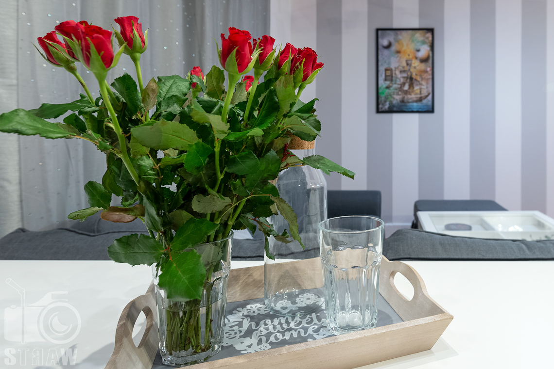 Sesja fotograficzna mieszkania na sprzedaż, kwiaty na tacy postawionej na blacie kuchennym.