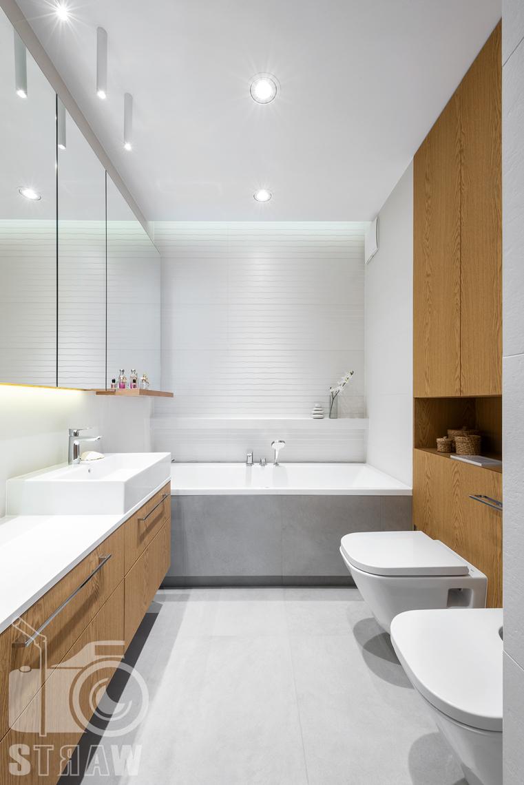 Fotografia wnętrz dla projektantów, zdjęcia mieszkania wykończonego według projektu biura projektowego 4ma Projekt, widok na całą łazienkę z wanną i umywalką.