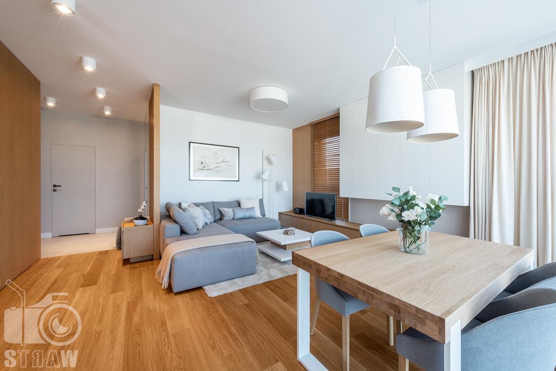 Fotografia wnętrz dla projektantów, zdjęcia mieszkania wykończonego według projektu biura projektowego 4ma Projekt, widok na salon ze stołem i sofą oraz przdpokój za ażurowym przpierzeniem..