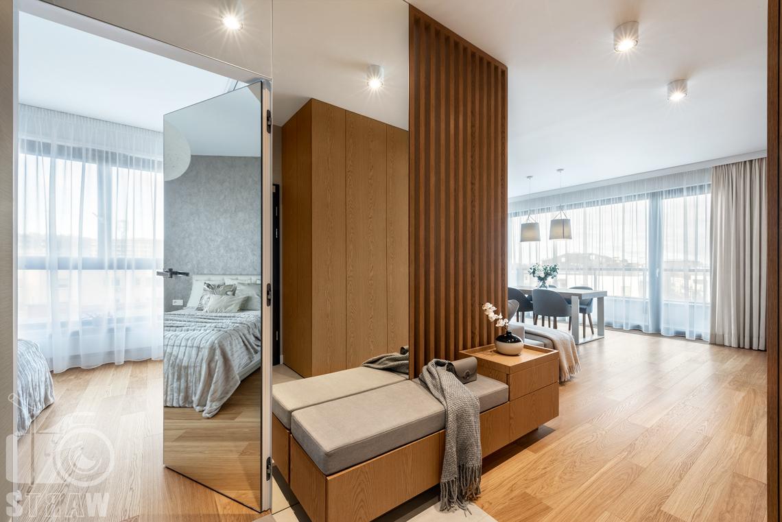 Fotografia wnętrz dla projektantów, zdjęcia mieszkania wykończonego według projektu biura projektowego 4ma Projekt, przedpokój, w tle stół w salonie oraz lustrzane drzwi do sypialni.