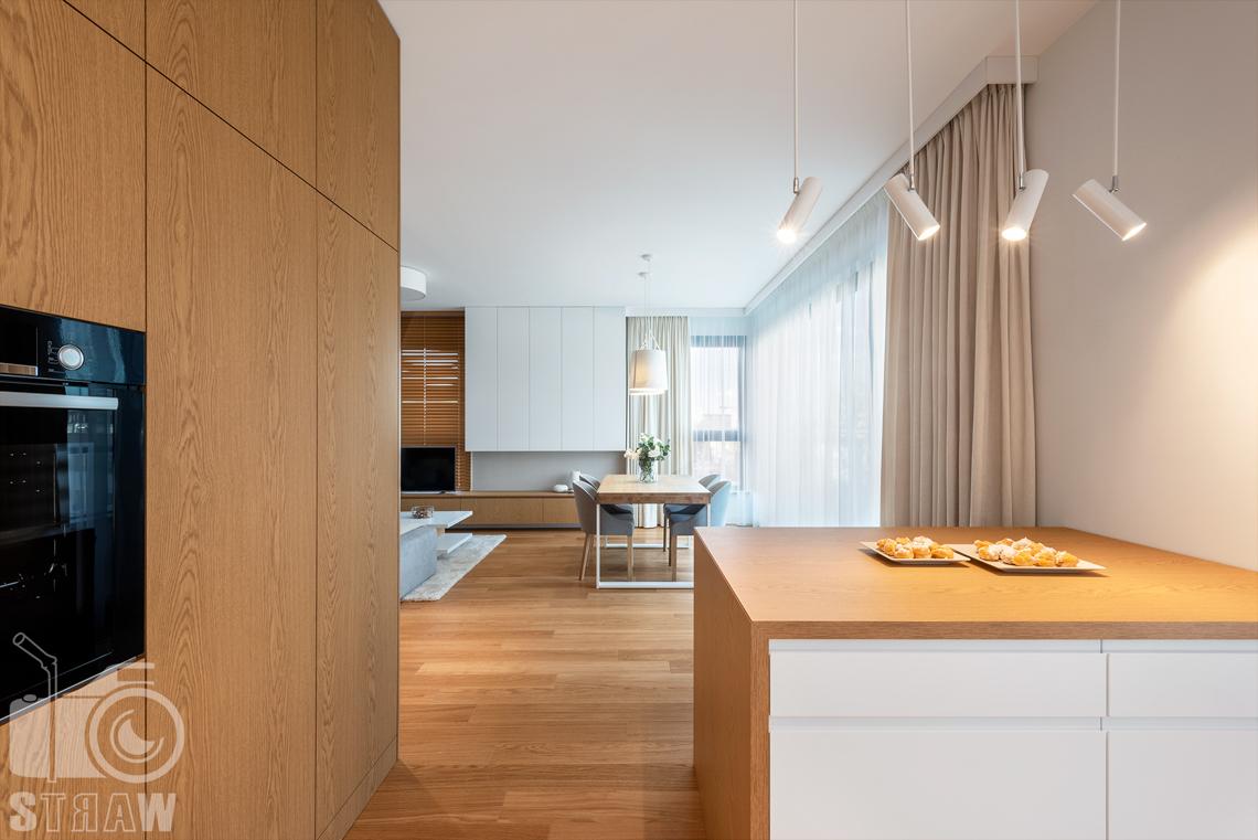 Fotografia wnętrz dla projektantów, zdjęcia mieszkania wykończonego według projektu biura projektowego 4ma Projekt, bufet kuchenny i widok z kuchni na salon.