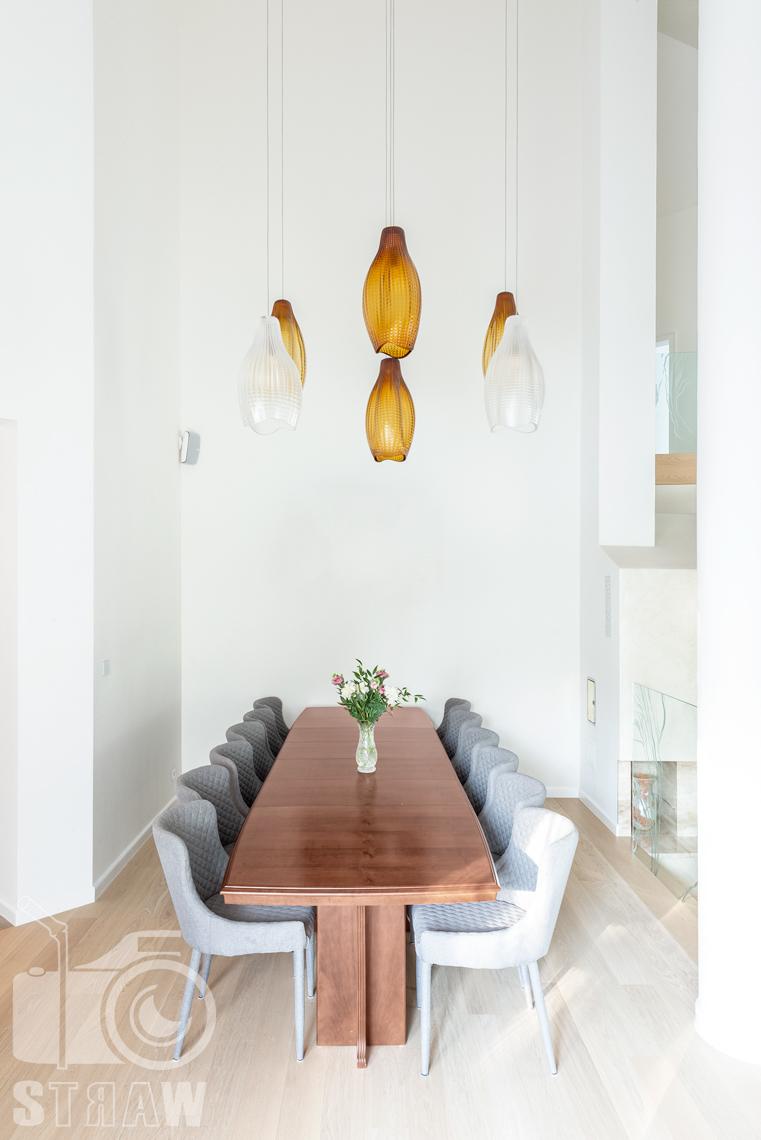 Fotografia wnętrz domu zaprojektowanego przez biuro projektowe, jadalnia i wiszące lampy nad stołem.