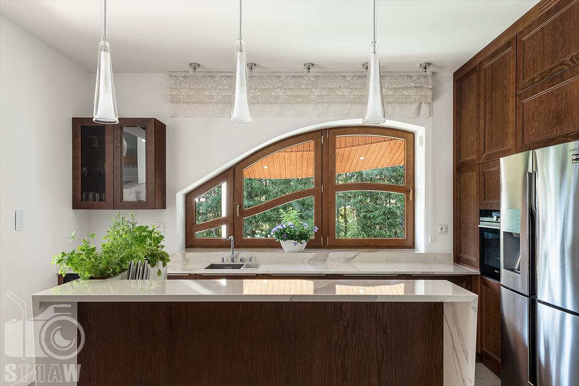 Fotografia wnętrz domu zaprojektowanego przez biuro projektowe, kuchnia, zabudowa kuchenna w drewnie, wiszące lampy i okno.